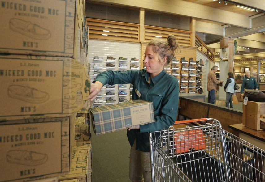 Abigail Schuster stocks moccasins at L.L. Bean's flagship store in Freeport. Schuster recently moved to Maine from Seattle and was hired in October as a temporary worker at the company, which hires about 5,700 seasonal workers annually.