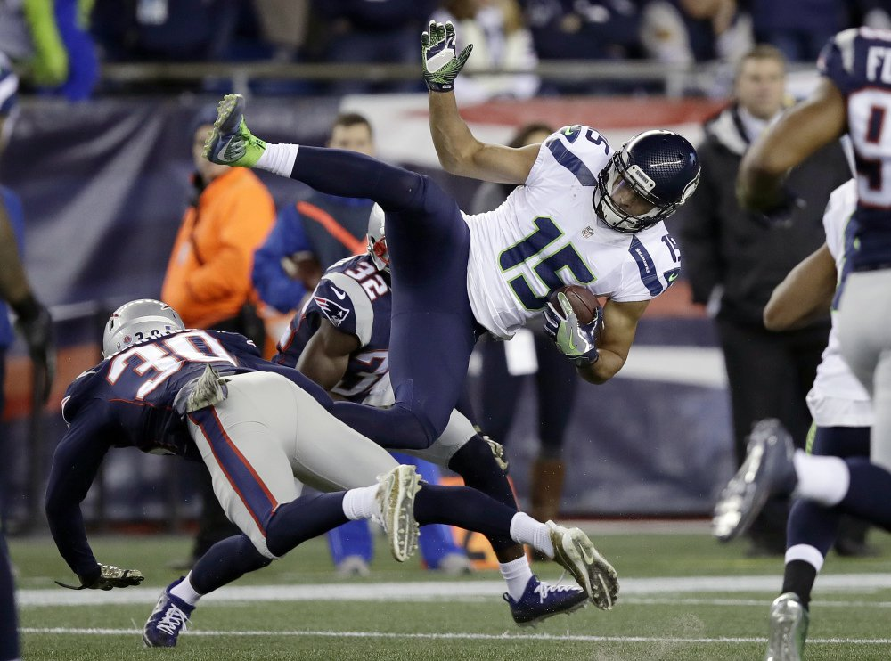 Seattle wide receiver Jermaine Kearse is upended by Patriots defensive backs Duron Harmon, left, and Devin McCourty after making a catch.