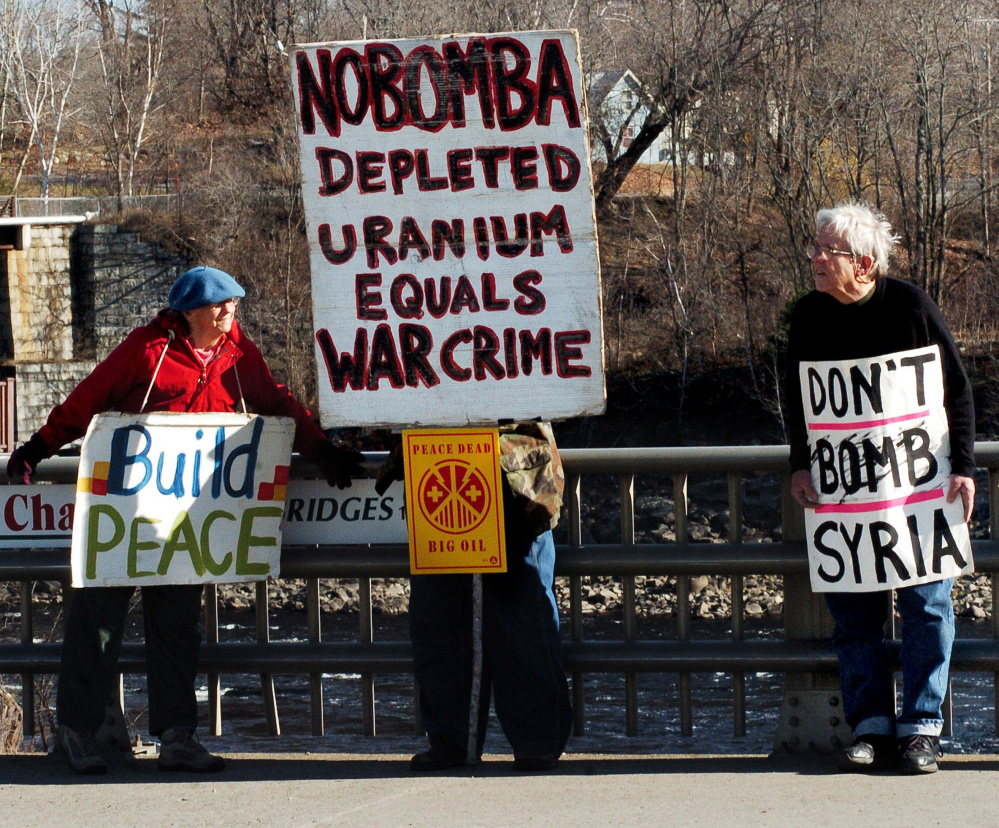 War protesters Lynne Harwood and Mark Roman hold signs Sunday on the Margaret Chase Smith bridge in Skowhegan.