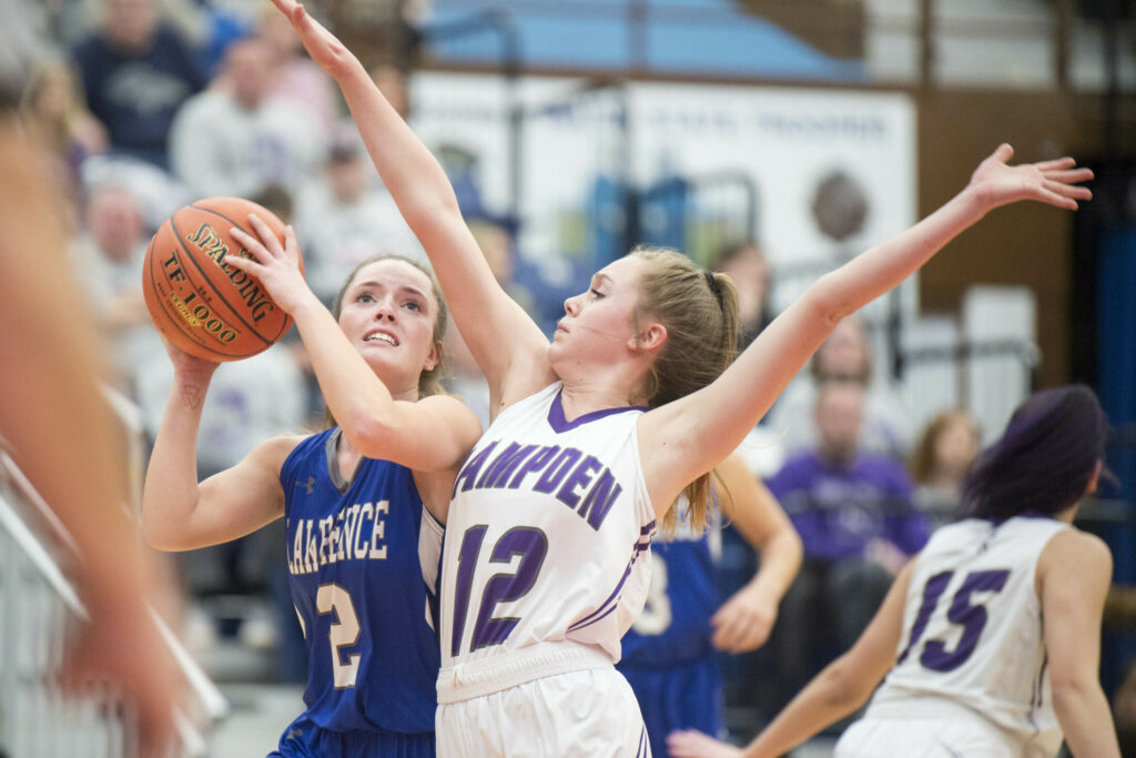 Lawrence's Megan Curtis (2) drives to the hoop as she is defended by Hampden's Amelia McLaughlin (12) in the first quarter in a Class A North semifinal game Tuesday at the Augusta Civic Center.