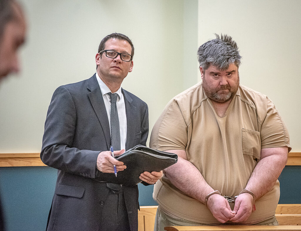 Steven Downs, 44, of Auburn, right, stands for his initial appearance in 8th District Court in Lewiston on Tuesday. Downs has been charged with the 1993 rape and murder of 20-year-old Sophie Sergie at the University of Alaska Fairbanks. Standing with Downs is attorney Richard Charest.