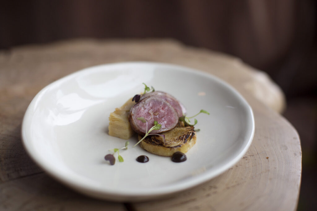 Bacon-wrapped lamb served with seared cabbage and a millefeuille of potato and celery root, black garlic puree and micro mustard greens at Hugo's.