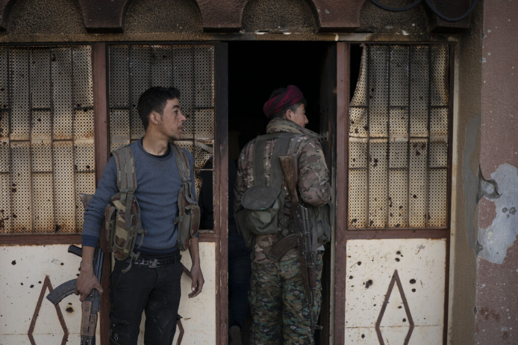 U.S.-backed Syrian Democratic Forces (SDF) fighters enter a building used as a temporary base near the last land still held by Islamic State militants in Baghouz, Syria, Monday, Feb. 18, 2019. Hundreds of Islamic State militants are surrounded in a tiny area in eastern Syria are refusing to surrender and are trying to negotiate an exit, Syrian activists and a person close to the negotiations said Monday.